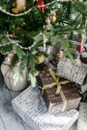 Vertical photo of new year present boxes under decorated christmas tree. Element of cozy interior with simple and craft package. Concept of preparation for december holidays