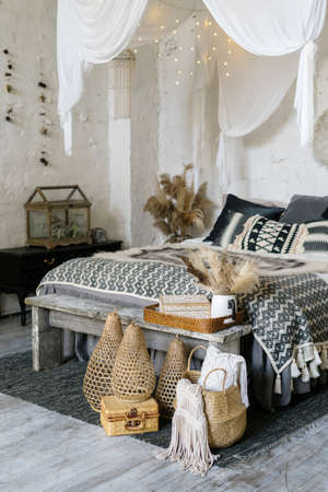 Vertical photo of cozy bedroom in bohemian interior with plaid, pillows and home decor in wicker basket. Wooden bench seat near comfort bed covered with warmth blanket 版權商用圖片