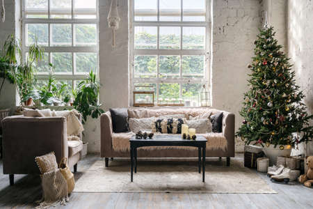 Concept of winter holidays decor in house. Cozy living room with comfortable couch, houseplants near armchair and coffee table on carpet. Christmas presents under decorated new year tree