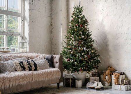 Cozy apartment in loft style with comfort couch near decorated new year tree and presents in bright living room. Christmas decoration in modern house with white wall on copy space background