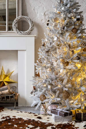 Vertical photo of cozy interior with simple and craft new year decorations on a christmas tree, presents and decorative fireplace in living room. Concept of preparation for winter holidays