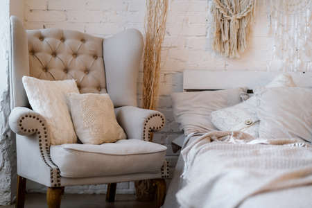 Comfortable armchair with cushions standing near bed in lovely bedroom with modern interior design in bohemian style