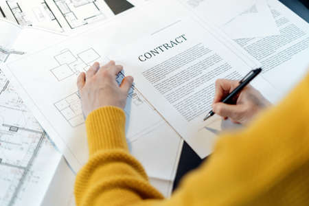 High angle view of woman reading contract, sitting behind table with project plan, analyzing real estate market, mortgage loan with low rate and signing agreement for buying property