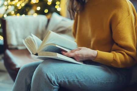 Concept of leisure and hobby. Cropped view of young woman reading paper book, turning pages, enjoying new interesting story, spending weekend at cozy home, sitting on comfortable couch in living room