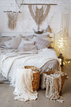 Vertical photo of wicker basket with textile standing near comfortable bed against blurred cozy bedroom interior design in boho chic style