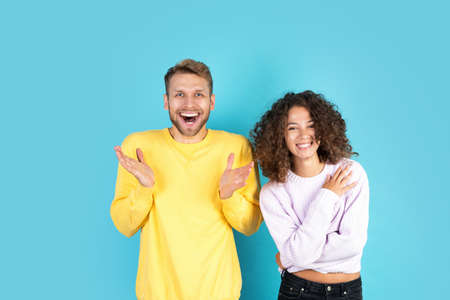 Two excited mixed race people standing together on blue background with copy space, making happy faces and raised hand up. Man and afro american woman celebrate winning Stock Photo