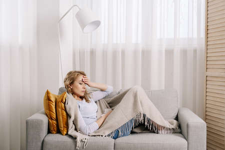 Concept of health problem. Sick and unhappy woman covered with plaid, touching forehead, suffering from strong headache or chronic migraine. Female sit on couch at home feeling pain in head