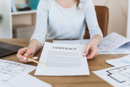 Selective focus on contract. Cropped view of businesswoman sitting in office behind desk, holding document and pen in hands, make offer to sign agreement, fill complete accurate details before deal