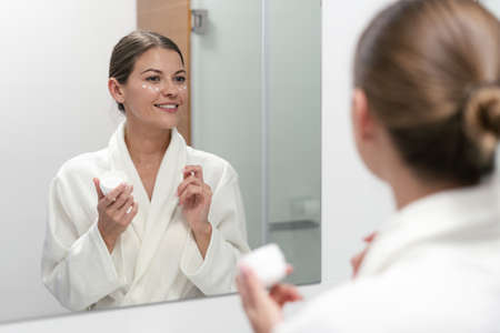 Selective focus of beautiful, young adult woman standing in bathroom, applying cream on face. She looking at mirror, holding jar with moisturizer in hands