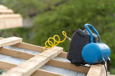 Concept of renovation, repair and fixing home. Close up photo of rooftop of new modern building construction. Pneumatic nail gun laying on roof cover of wooden framework house with blurred backgroung