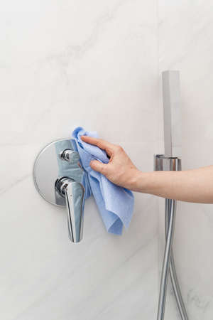 Housework and housekeeping concept. Vertical view of cropped woman cleaning water tap in shower cabin, wiping new plumbing with rag, standing in bathroom