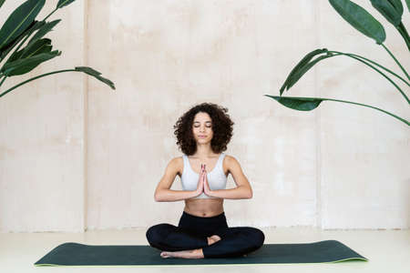 Peaceful african american woman in black sportswear sitting on fitness mat in meditation pose with praying hands. Sporty and mindfulness girl doing breathing exercise, training in yoga class