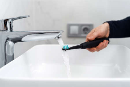 Cropped view of woman holding modern electric and wireless toothbrush under running water, over sink. Female brushing teeth in the morning, standing in bathroom at home