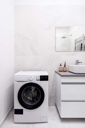 Vertical view of bathroom with automatic washing machine, modern interior design, mirror over sink against ceramic tile wall. Electric toothbrush and soap dispenser bottle near basin