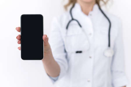 Cropped view of family doctor in white medical uniform hold modern smartphone with empty blank screen and copy space for advertising product or service. Woman holding modern gadget with mockup display
