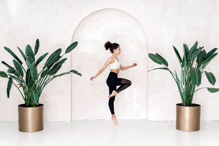 Happy afro american woman jumping up against copy space wall in room with houseplants. Sporty girl training in fitness center, making cardio workout in sport club or home
