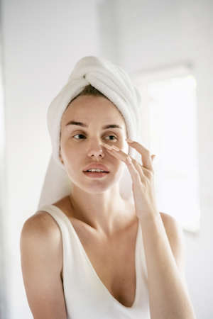 Vertical view of young adult female looking at her face, touching her perfect skin and standing in white bathroom with towel on head, making daily routine procedure Reklamní fotografie