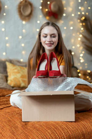 Dreamy and smiling young adult woman unpacking delivered carton box, holding new red shoes in hands, looking at footwear and making happy face