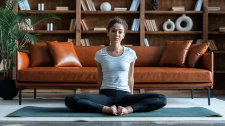 Panoramic view of afro american woman making sport training at home, sitting on exercise mat in living room, practicing yoga, working out. Sporty and fit girl in sportswear looking at camera