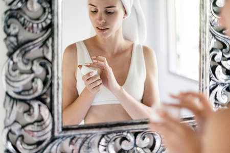 Young adult girl holding natural face cream in hands, standing near mirror in white bathroom with towel on head, making daily routine procedure