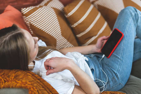 Young adult woman using earphones, modern smartphone with copy space on empty display, listening music and spending free time at home, lying on couch in living room