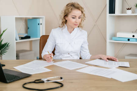 Medicine and healthcare concept. Doctor in white uniform sitting behind work desk with stethoscope. Woman physician read notes, fill patient form, write medical history or anamnesis in journal Stockfoto