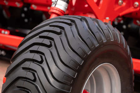 Close up view of new black wheel and clean protector on tractor tire. Concept of agricultural machinery for harvesting on countryside farm on outdoor exhibition 免版税图像