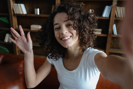 Happy afro american woman looking at camera, smiling wide, waving hand and make self portrait. Blogger or social influencer talking at video call with friends in online app 免版税图像