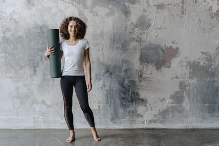 Sport coach preparing for fitness workout on yoga class. Young afro american woman wear sportswear standing with rolled exercise mat against copy space background 免版税图像