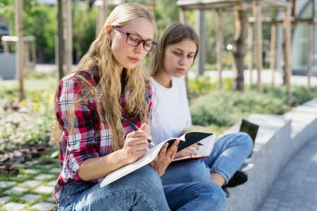 Education concept. Two smart and young university student girl study together, making scientific homework project, spending time near campus, writing notes in copybooks