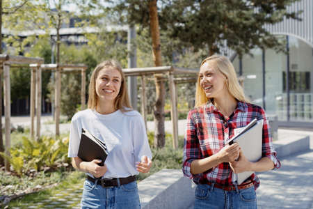Education concept. Two happy and smiling young student girl study together, spending time near campus, walking outdoors with copybooks in hands, laughing and talking to each other