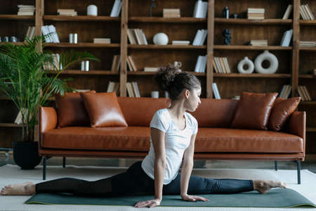 Profile view of young afro american woman in sportswear stretching legs, doing splits sitting on floor in living room. Female in daily workout make yoga training on exercise sport mat at home