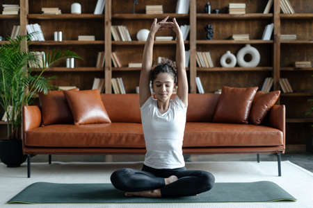 Afro american woman in sportswear raised hands, stretching upper body, warming up before workout at home. Female doing fitness training on yoga mat in living room 免版税图像