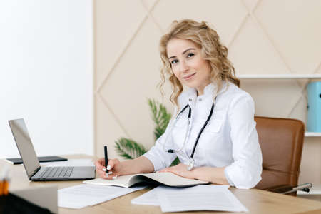 Medicine and health care concept. Woman doctor in white uniform working in personal cabinet, sitting behind desk in private clinic, fill patient form, make notes prescription to hospital client 免版税图像