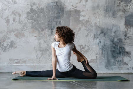 Young afro american woman in sportswear stretching legs, doing splits. Flexible female make sport training on fitness mat. Girl workout on floor against copy space background in yoga class