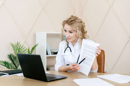 Woman doctor using laptop computer, make video call, showing medical insurance to patient at online consultation. GP in white coat sitting behind desk in hospital office, working remotely with people 免版税图像 - 167485771
