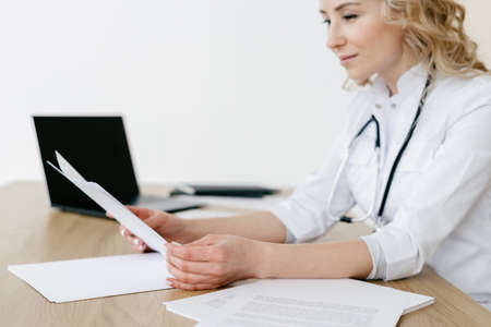 Woman doctor in white coat check medical insurance, working in private clinic with documents. Professional medic nurse look at patient health report, sitting behind desk in office 免版税图像 - 167485640