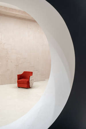 Concept of modern architecture and contemporary interior design. Vertical view of red velvet armchair in empty room with loft style. Furniture against concrete wall with copy space near stairs