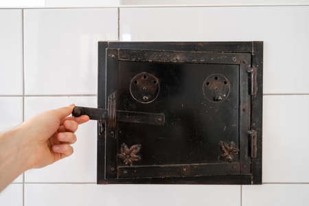 Close up photo of man hand opening the iron door of warming oven on wood burning stove made of glazed white tiles. Heating and traditional cooking appliances concept