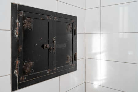 Close up photo of iron baking oven door on wood burning stove made of glazed white tiles with copy space on background wall, cropped shot. Heating and cooking appliances concept