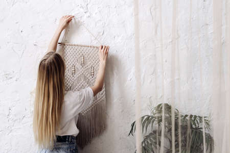 Back view of young adult woman hangs white handmade macrame on the wall in room with cozy interior. New cotton knitting with natural material in boho style bedroom. Home decor concept