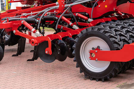Agriculture equipment for soil cultivation. Close up view of new red tractor plow for land cultivation. Tractor with plow standing outdoors on exhibition