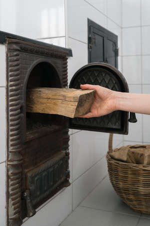 Cooking with minimum environmental impact. Vertical shot of male hand putting firewood in opened firebox of wood burning stove made of glazed white tiles. Traditional home heating concept