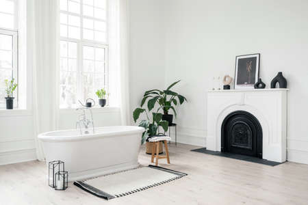 White classic freestanding bathtub, large windows, modern fireplace and green houseplants in light bathroom with scandinavian interior design. Concept of home decor in contemporary apartment