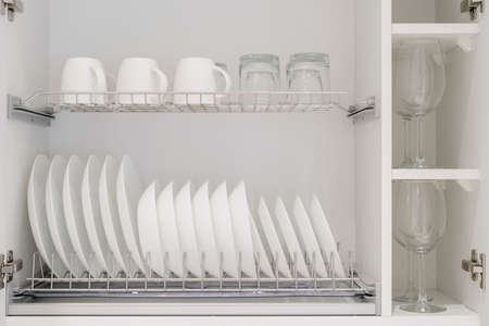 Set of clean white dishes, mugs and different glasses and other crockery in opened white kitchen cupboard shelf. Close up of storage cabinet with kitchenware inside
