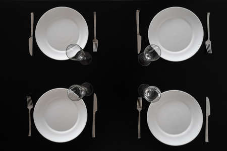Top view of dark kitchen table setting for dinner for four persons, white plates, wineglasses and cutlery. Dinnerware set concept