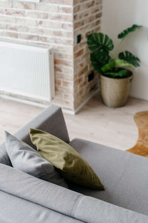Vertical shot of modern gray couch with decorative pillows in loft style living room or lounge zone decorated with potted greenery, white radiator hanging on brick wall in blurred background