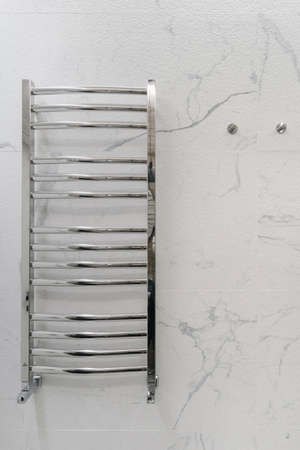 Vertical shot of shiny straight chrome heated radiator in simple design with coated towel rails mounted on modern bathroom gray marble tile wall 免版税图像