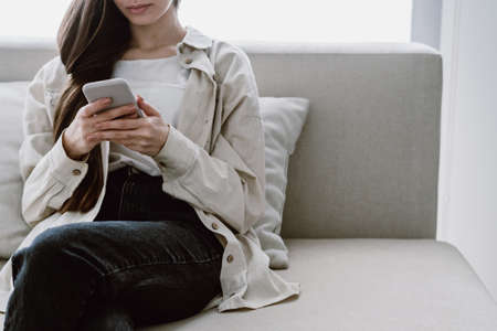 Online application concept. Cropped view of young woman in casual wear using her modern smartphone, send text message, reading news at website. Female sitting on comfort sofa in living room 免版税图像