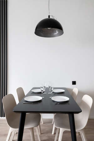 Vertical shot of large black kitchen table setting for family dinner with dinnerware, wineglasses and cutlery with hanging metal lamp above and white chairs in minimalistic interior design